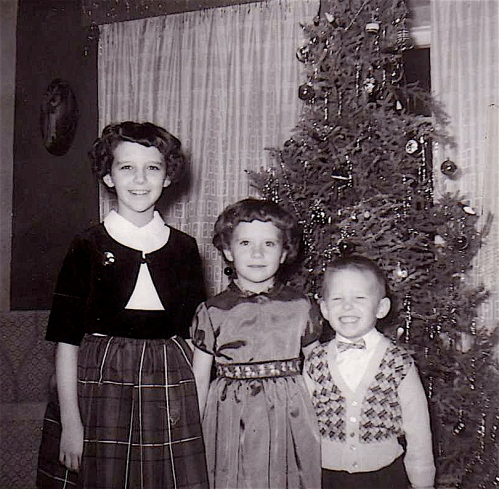 with my siblings around the christmas tree