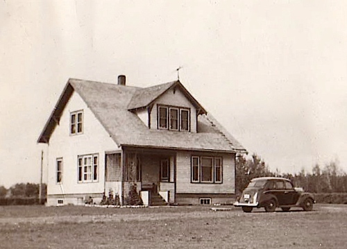My grandparents' car standing outside their farmhouse in Drake, Saskatchewan