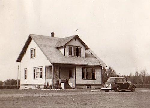My grandparents' car standing outside their farmhouse in Drake, Saskatchewan