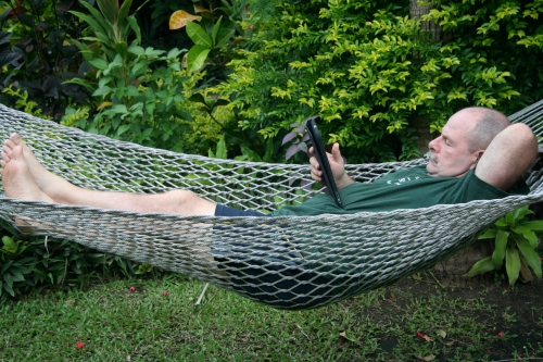 man reading kindle in hammock