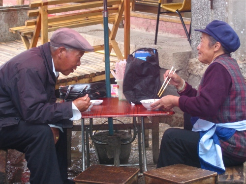 elderly chinese couple eating lunch with chopsticks outdoors in yunnan