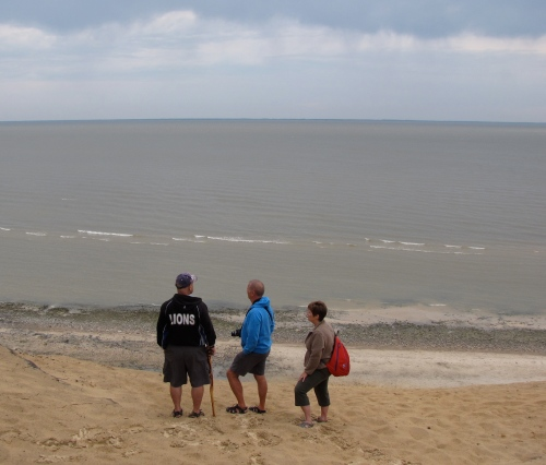 three people on the shore of lake winnipeg