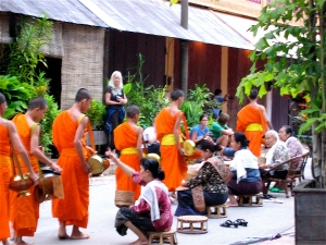 women giving monks sticky rice in luang prabang