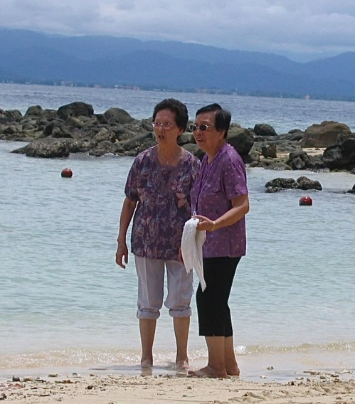 supporting each other elderly women on the beach in malaysia
