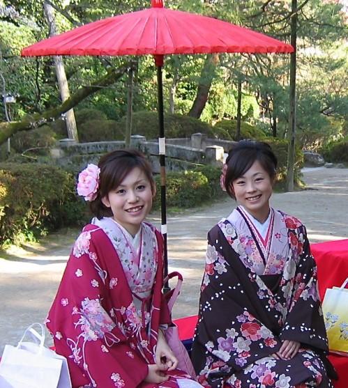 Women in kimonos pose happily for tourists