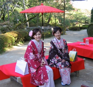 Women in kimonos pose happily for tourists