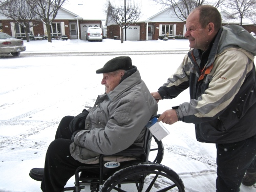 Dave pushes his Dad through the snow to a Christmas party. They are singing Leise Reiselt Der Schnee