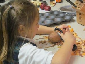 little girl peeling potatoes