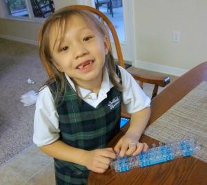 little girl using the rainbow loom