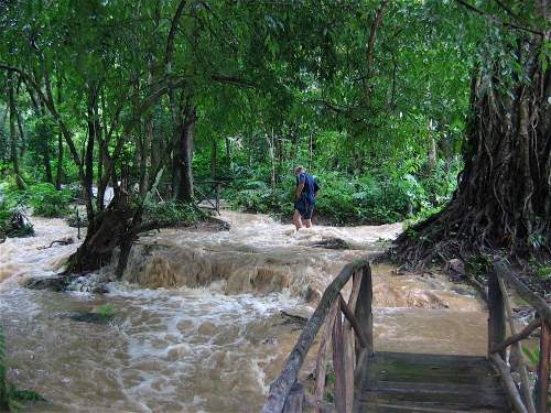 hiking through rushing water laos