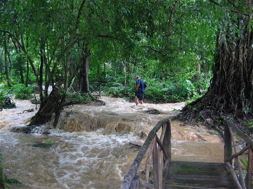 hiking through rushing water laos