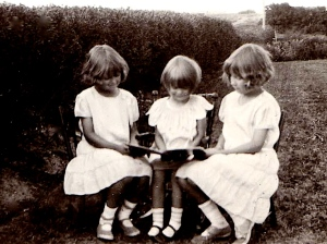 My mom reading with her sisters around 1933. Check out their nice shoes.