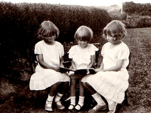 My mom reading with her sisters around 1933.