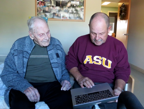 Dave and his Dad look at pictures of his great grandson on the computer