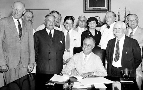 Frances Perkins stands behind President Roosevelt as he signs the social security act in 1935 a lasting legacy of Frances Perkins