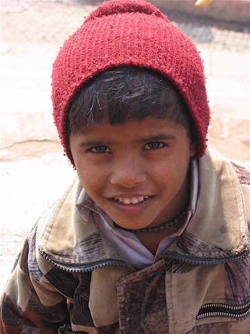 boy in india in red toque