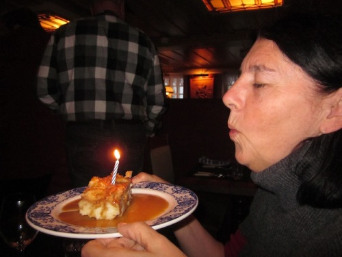 blowing out candle on bread pudding