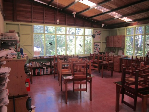 Typical classroom at the school with lots of windows open to the forest surrounding the school. Bird cutouts on the windows prevent the many birds in the surrounding woods from being injured.