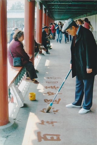 man drawing letters tiananmen square