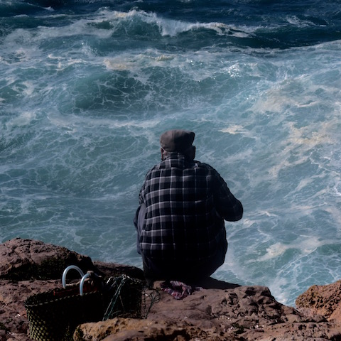 fisherman perched on cliff at sagres