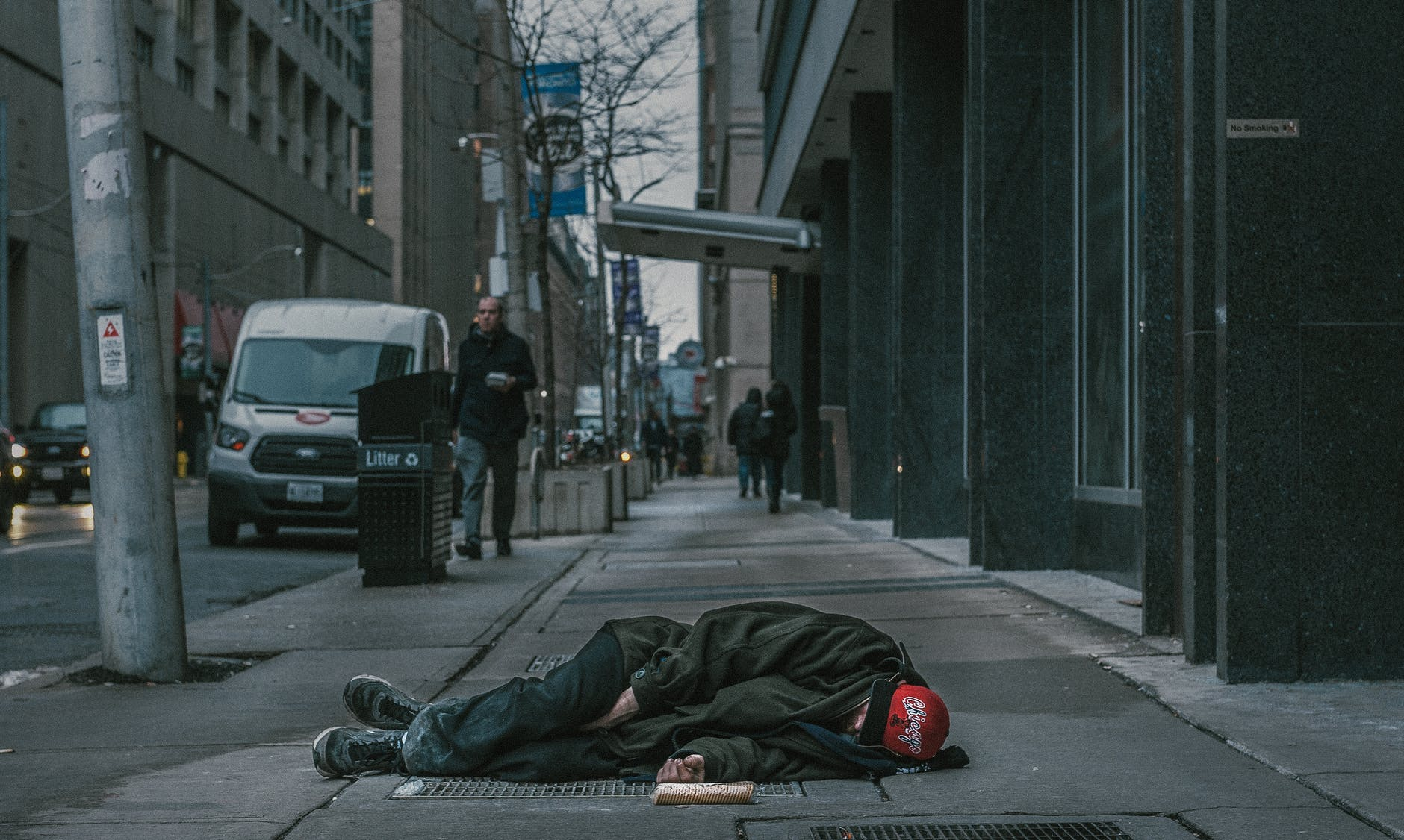 photo of man laying on sidewalk